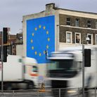 Lorries pass the Brexit-inspired mural by artist Banksy in Dover. Photograph: Gareth Fuller/PA.