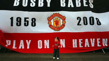 A Manchester United fan poses for a photo, as fans take part in a minute's silence to mark 50 years
