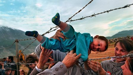Agim Shala, 2 years old, is passed thru the barbed wire fence. Photo: Carol Guzy/Washington Post/Get