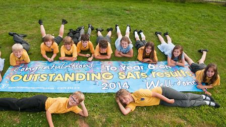 Year six school leavers with a well done banner for their outstanding SATs results.