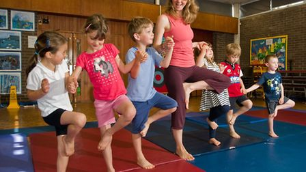 Yoga teacher Kathryn Chandler with some reception pupils.