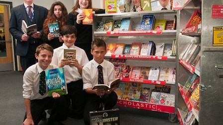 Head teacher Chris Wade with students looking through the books on sale in the library.