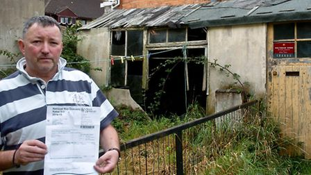 Kieron Morris with the letter from the council asking for business rates for old shack at the back o