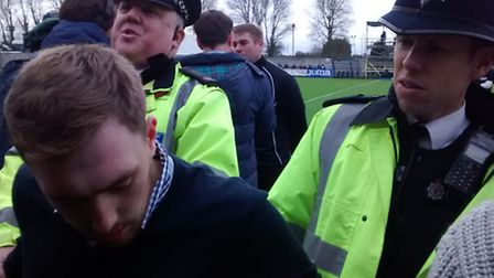 A Doncaster fan who invaded the pitch is led away by police.