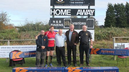 Staff from Kellaways hand over new post protectors to rugby club.