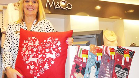 Sarah Griffiths at M&Co prepares Christmas stock for Portishead's late night seasonal shopping