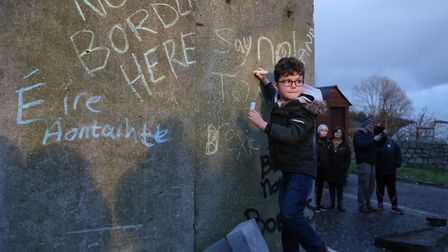 A boy writes a message on concrete blocks that were temporarily installed as part of an anti-Brexit