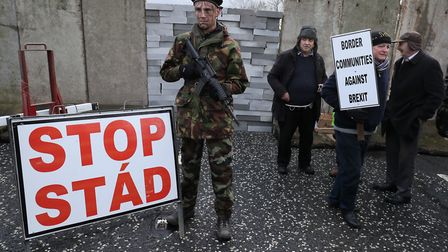 People take part in an anti-Brexit rally at the Irish border near Carrickcarnan, Co Louth, expressin