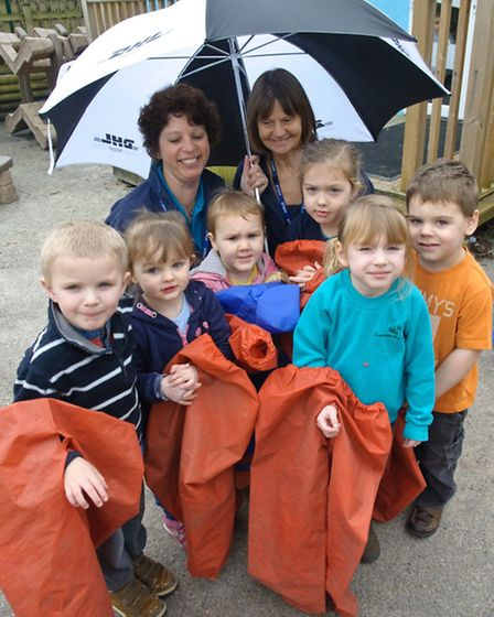 Sarah Hayett and Debbie Davie with children showing the holes in their current waterproofs.