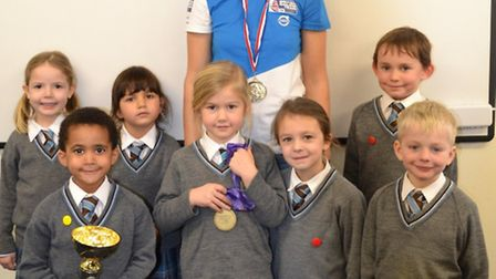 Noelle Finch letting children hold her windsurfing medals at Fairfield School.