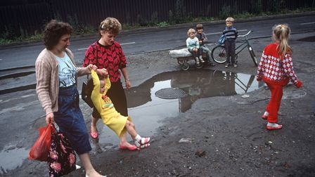 Mothers swing a child across a filthy puddle in the town of Nova Huta, an industrial Stalinist steel
