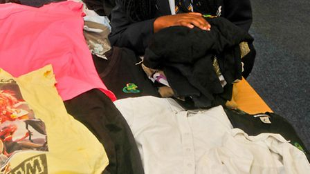 Kimberely Phiri pupil from Gordano School Portishead with piles of old schol uniforms she is sending