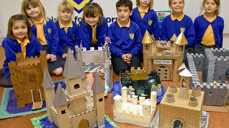 Pupils showing off model castles that they have built.
