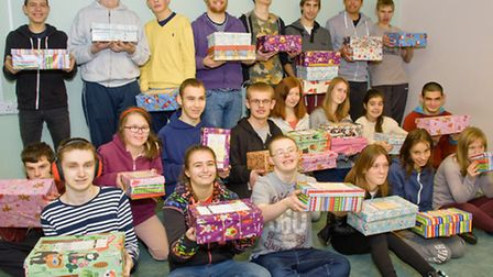 Students with the boxes they have filled with Christmas gifts.