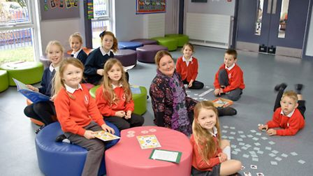 Children working with their teacher in the new hall section.