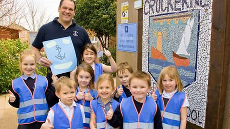 Chairman of Pill Hobblers Marine Services, Marcus Stratton and school children with some of the vest