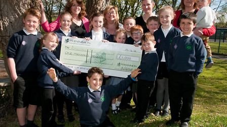 Carole Negus from Persimmon Homes presents the £1000 cheque to staff and pupils of Kingshill school.