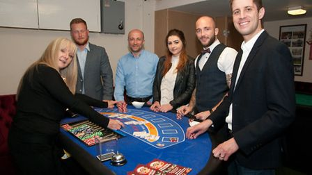 Chairman Mark Williams with guests at one of the blackjack tables.