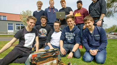 The Year 13 team seated with their robot pictured with the year 12 team and D&T Technician Richard M