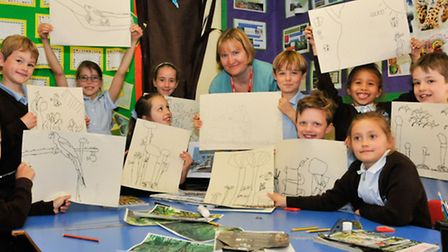 Artist Emmeline Simpson with year 3 pupils and their rainforest themed artwork.