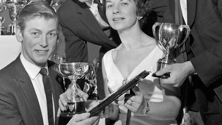 Secretary, Mollie Bliss is Shown some of the trophies won by Roger Hutchings, Michael Lock and Peter