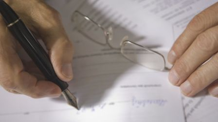 Close-up of a person's hand filling a form. Picture: Getty Images/iStockphoto