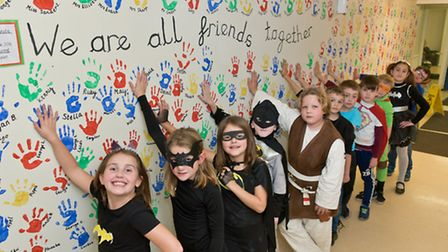Pupils dressing as superheroes with their Wall of Power for anti-bullying week.
