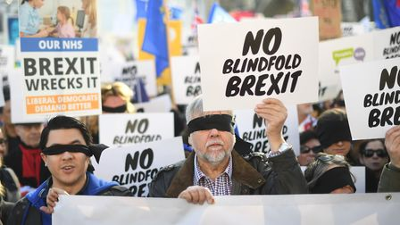 People's Vote supporters wearing blindfolds and carrying placards assemble in Parliament Square ahea
