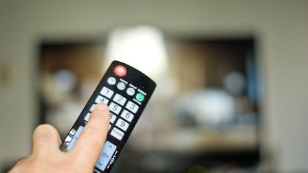 Hand with remote control pointing at TV