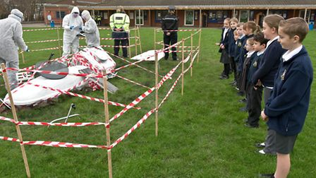 Pupils with police/fire brigade members by rocket debris.