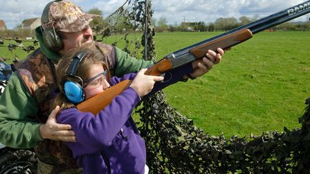 Rob Collins of Really Wild Adventures teaching scout Lily how to shoot.