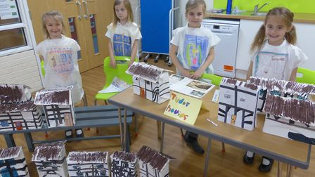 Pupils show off the Tudor clothes and houses they have made.