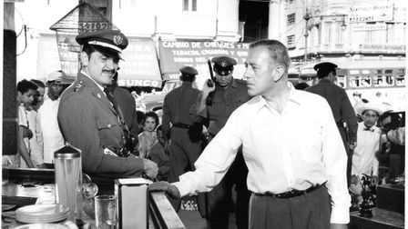 Ernie Kovacs and Alec Guinness standing at bar in a scene from the film 'Our Man In Havana', 1959. (