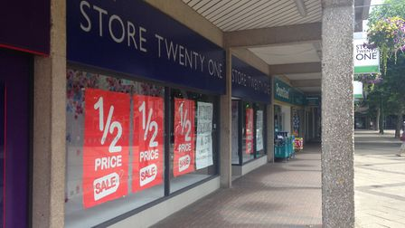 Clothing retailer Store Twenty One with sale signs in the window.