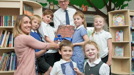 Ribbon being cut by author Amy Wilson, watched by pupils and headteacher Peter Treasure-Smith .