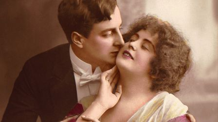 Hand tinted photograph shows a man in evening dress kisses a woman's cheek and embraces her, early 2