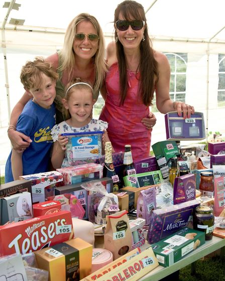 Sian Horne and Helen Woodward running the tombola with the help of Sam and Brook
