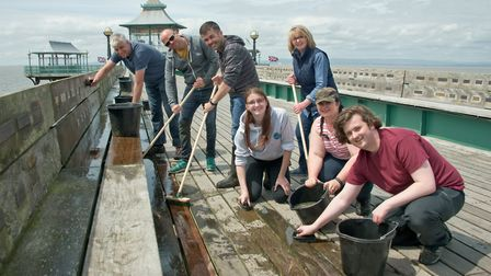 The Agilisys team scrubbing the decks at Clevedon Pier.