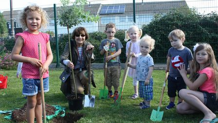 Cllr Jan Barber and some helpers plant the tree at the children's centre and library in Worle.