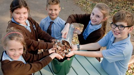 St Francis Primary School pupils mearsuring some of coins collected by their classmates.
