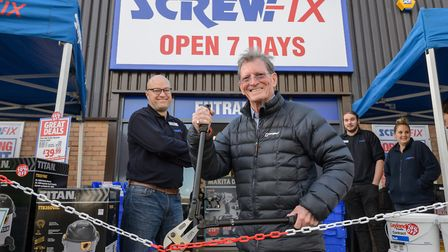 Store manager Dan Clark cuts the ribbon with former Coronation Street actor Johnny Briggs.