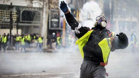 A yellow-vest protester throws back a teargas canister toward police officers near the Arc De Triomp