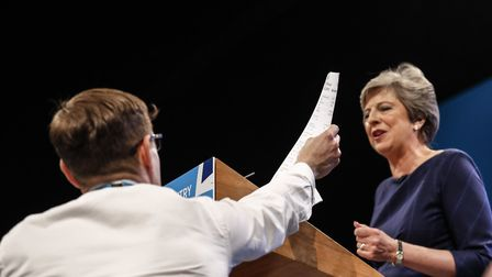 Theresa May is handed a P45 note during her conference speech in Manchester, Britain. (Xinhua/Han Ya