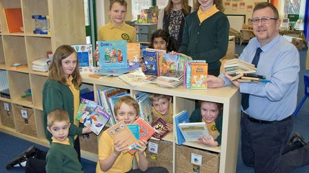 Vicky Angear handing over books to St John Primary School pupils and their headteacher Ian Doswell.