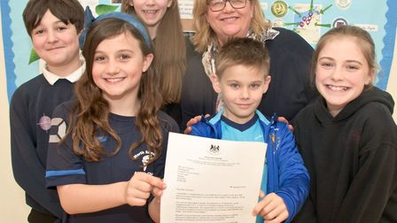 Headteacher Jan Thomson and pupils with the letter they received a letter from the minister of state