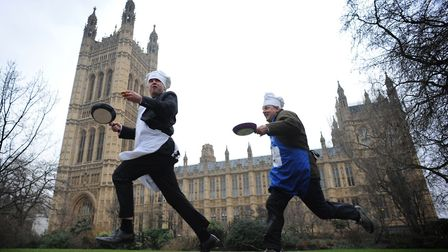 MPs, Lords and members of the press take part in pancake races outside the Houses of Parliament in L