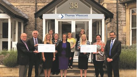 The team from Thomas Westcott Chartered Accountants handing over their donations.