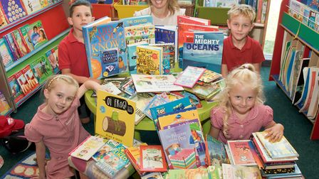 Teacher Emma Caffrey with pupils and the 100 books.