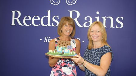 Candy Minshall and Rozzanna Farbrace from Reeds Rains with the cake.