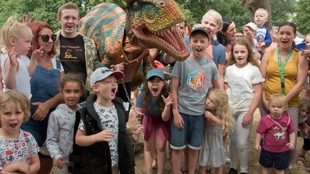 Youngsters partying in the park with a dinosaur.